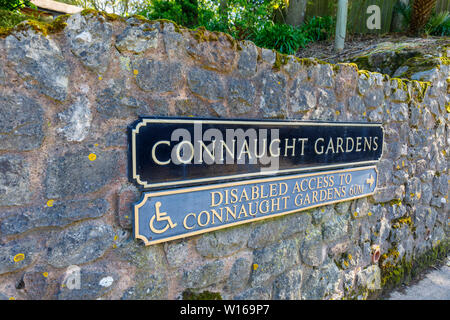 Name sign on a wall at the entrance of Connaught Gardens, Sidmouth, a small popular south coast seaside town in Devon, south-west England - Stock Image