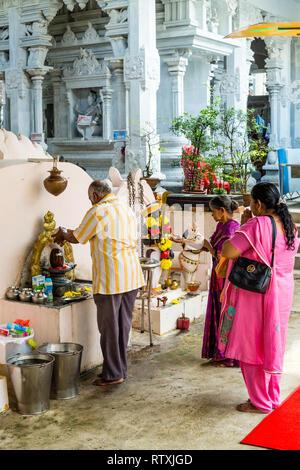 A Worshiper Pours Water over the Shiva Lingam upon entering the Hindu Sri Maha Muneswarar Temple, Kuala Lumpur, Malaysia. - Stock Image