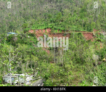 A road and mountainside near Barrio La Torres have been damaged by Hurricane Maria November 2, 2017 in Lares, Puerto - Stock Image