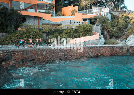 Group of multiple people exercising. Yoga retreat Puerto Vallarta - Mismaloya, Mexico. Horizontal photo. - Stock Image