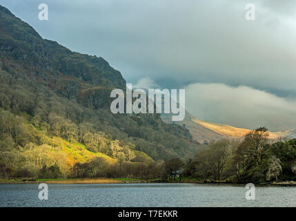 Llyn Gwynant lake looking north with a grey aspect and some lovely sunny splashes. A Snowdonia National Park landscape, North Wales - Stock Image
