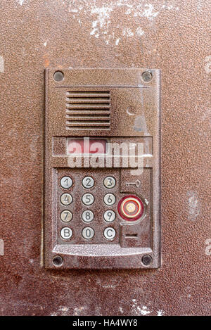Vertical composition of an electronic door entry keypad in brown metal. - Stock Image