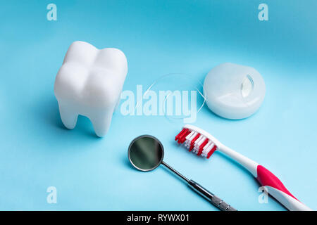 Close-up Of White Artificial Tooth And Dental Equipment On Blue Backdrop - Stock Image