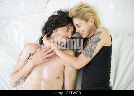 A cool young tattooed couple cuddling on a bed. - Stock Image