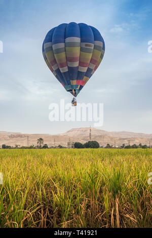 Hot air balloon flying over Valley of the Kings, Luxor, Egypt - Stock Image