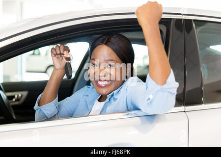 cheerful young African woman showing her new car key at dealership - Stock Image