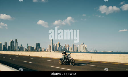 Man Riding Motorcycle in Panama City With Skyline in Background - Stock Image