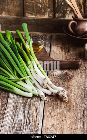 Fresh springtime green onion and garlic on rustic wooden background, plant based food cooking  ingredients - Stock Image