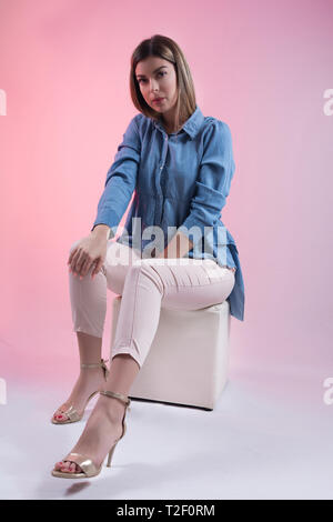 Cute young woman in blue jeans shirt and high heels on leg sitting on white cube stool in studio and isolated on pink background. Female fashion - Stock Image