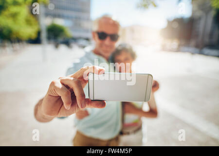 Happy senior couple embracing and taking a self portrait on mobile phone outdoors. Tourist taking selfie, focus - Stock Image