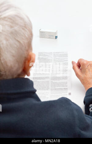 Old woman sitting at a table in her living room unable to read the information sheet of her prescribed medicine, because the print is too small - Stock Image
