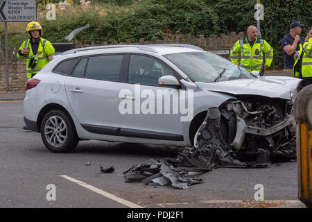 Smashed up renault estate car with emergency service personnel in the background after a head on collision - Stock Image