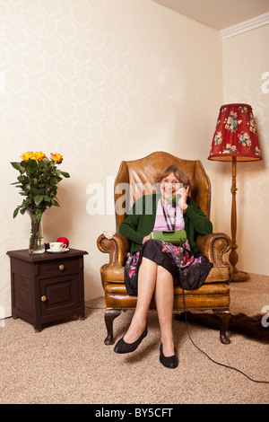 A senior woman on the phone at home - Stock Image