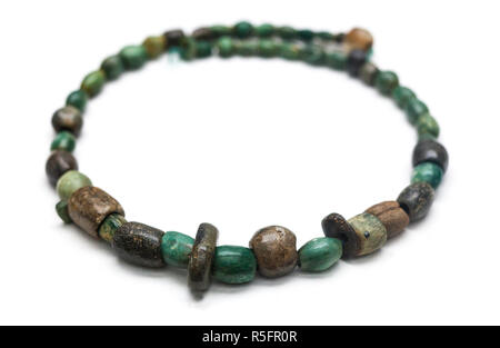 Huelva, Spain - July 7th, 2018: Copper Age Polished Necklace made with malachite stone beads. Isolated over white background - Stock Image