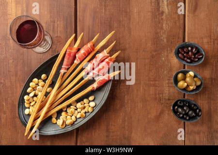 Prosciutto-wrapped Italian grissini with wine, almonds, and olives, overhead view. Italian antipasti with parma ham, shot from the top - Stock Image