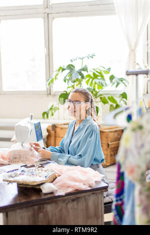 Pleasantly looking wearing ponytail is sitting at her worktable with laid tailoring equipment, containers full of thread spools, thinking of color whi - Stock Image