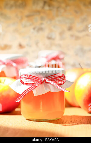 Homemade apple jelly in glass jars with linen cover and a nostalgic ribbon bow in bright sunshine in front of an old stone wall, copy or text space - Stock Image