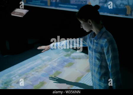 Woman using interactive display with no touch control technology - Stock Image