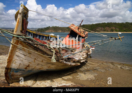Frontal view of an old fishing boat turned on a side, wrecked and rotting on a rocky bank by the Mira River bank. - Stock Image
