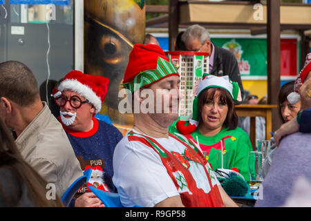 Benidorm, Costa Blanca, Spain, 25th December 2018. British tourists dress for the occasion on Christmas Day in this favourite getaway destination for Brits escaping the cold weather at home. Temperatures will be in the mid to high 20's Celsius today in this mediterranean hotspot. People outside bar wearing  Christmas jumpers and santa hats. - Stock Image