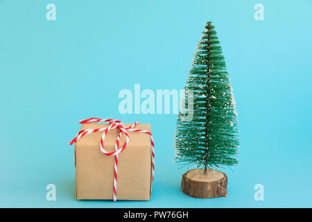 One gift box wrapped in craft paper tied with red white ribbon Christmas trees on light blue background. New Year corporate presents shopping concept. - Stock Image