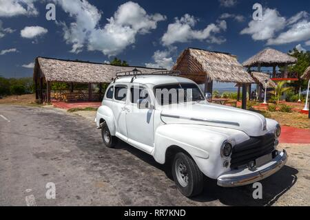 Vintage Old White Cuban Car against the background of Open Houses and Blue Sky dotted with puffy Clouds in Guantanamo Province, Cuba - Stock Image