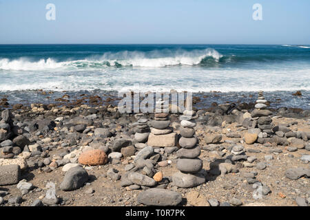 Waves breaking along the shore with stone cairns or piles of stones in the foreground in Costa Adeje, Tenerife, Canary Islands. - Stock Image