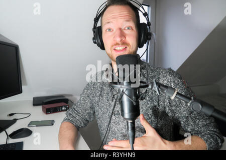 Young male behind condenser microphone radio podcast host voice recording - Stock Image