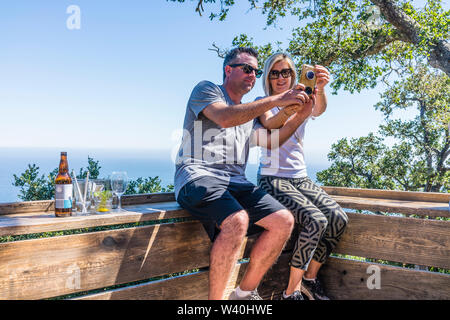 An adult couple sits on a wooden bench, overlooking the California Central Coast and takes a selfie to document their trip. - Stock Image