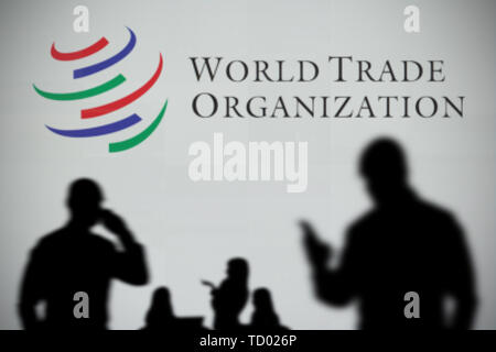 The World Trade Organization logo is seen on an LED screen in the while a silhouetted person uses a smartphone in the foreground (Editorial use only) - Stock Image