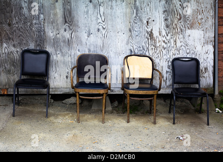 old chairs sitting against wall in alley - Stock Image