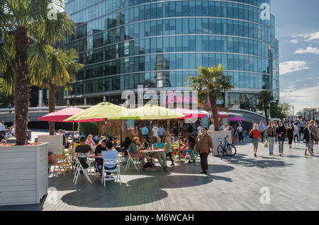 People sitting in summer sunshine at the London Riviera pop up restaurant on the Southbank, London, UK - Stock Image