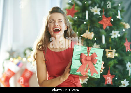 cheerful modern woman in red dress near Christmas tree green Christmas present box - Stock Image