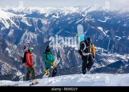 Snowboarders hiking to the summit of La Capa to ride the fresh powder. - Stock Image