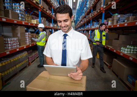 Warehouse manager using digital tablet - Stock Image
