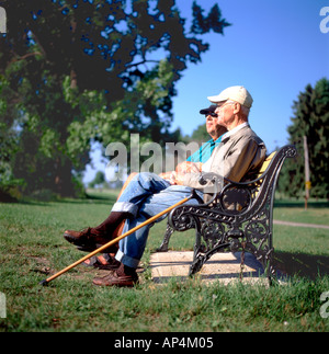 Two elderly men sitting on a park bench reminiscing at Niagara Park in Fort Erie, Ontario, Canada   KATHY DEWITT - Stock Image