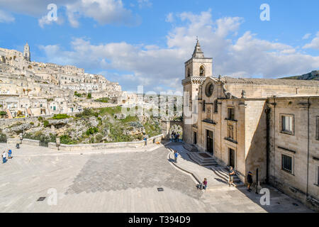 Tourists enjoy a summer day on the piazza of the Church of San Pietro Caveoso with the medieval hillside village and ancient sassi in view - Stock Image
