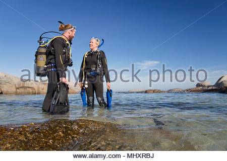 Couple in wetsuit going ocean scuba diving from beach - Stock Image