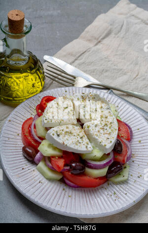 Traditional greek salad made with fresh cucumber, tomato, paprika, red onion, kalamata olives, white salted feta cheese with oregano served with olive - Stock Image