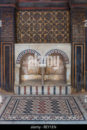 Wooden wall decorated with painted floral patterns, embedded arched niche and marble floor decorated with geometric patterns - Stock Image