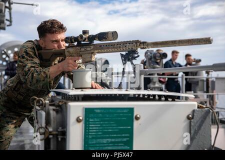 180828-N-AO674-1135 ATLANTIC OCEAN (Aug. 28, 2018) A U.S. Marine assigned to the 22nd Marine Expeditionary Unit scans for surface contacts while standing a force protection watch during a simulated transit aboard the Wasp-class amphibious assault ship USS Kearsarge (LHD 3) as part the Carrier Strike Group FOUR (CSG 4) Amphibious Ready Group, Marine Expeditionary Unit exercise (ARGMEUEX). Kearsarge Amphibious Ready Group and 22nd Marine Expeditionary Unit are enhancing joint integration, lethality and collective capabilities of the Navy-Marine Corps team through joint planning and execution of  - Stock Image