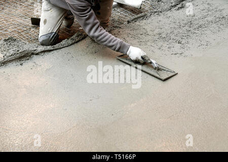 Construction worker on his knees flattening cement mortar with hand spatula while a making concrete floor - Stock Image