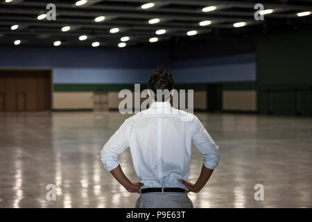 A businessman standing in a dimly lit and dark exhibition area in a convention center. - Stock Image