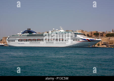 The P&O Cruises cruise ship Oceana by the walls of Valletta in Malta's Grand Harbour. Travel and tourism in the Mediterranean Sea. - Stock Image