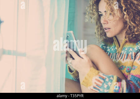 Blue cold vintage tone colors image with beautiful young caucasian woman looking and using a modern phone at home with a little surprised expression - - Stock Image