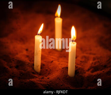 A votive candle or prayer candle is a small candle, typically white or beeswax yellow, intended to be burnt as an offering. - Stock Image