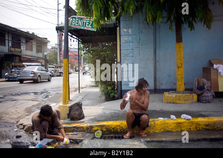 Two poor Filipinos bathe using water in a gutter in Manila, Philippines. - Stock Image