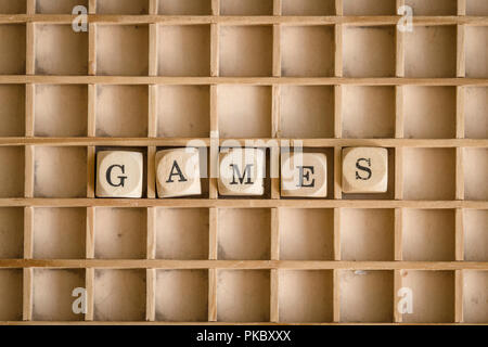 Games word written with dices on a wooden board - Stock Image