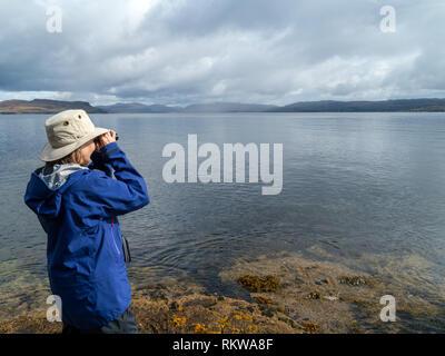 Woman using binoculars to spot marine wildlife in sea Loch Slapin, Isle of Skye Scotland, UK - Stock Image