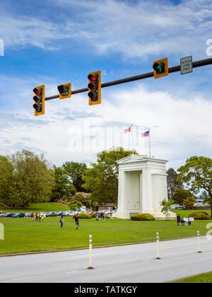 May 26, 2019 - Surrey, BC: Red traffic control light above road to border with Canada-USA Peace Arch Monument and park in background. - Stock Image